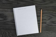 Shopping list phrase in notepad with chequered pages on gray wood table and Stock Photos