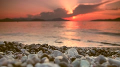 Tranquil beach sunset scene. Close focus, distant subjects out of focus. - stock footage