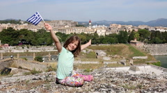 Happy little girl waving with Greek flag Corfu town Greece Stock Footage
