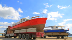 EDITORIAL. Two Trucks With Sailboats Aboard At Seaside Stock Footage