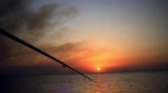 Fisherman sport hobby fishing rod or spinning reel on sea beach during sunset Stock Footage