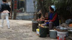 Senior woman preparing food to sell at street market in Dali - stock footage