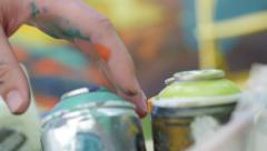 Slow motion of writers hand picking spray can Stock Footage