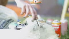 Slow motion of writers hands picking spray cans Stock Footage