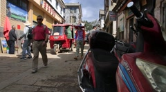 Motor tricycles and bikes on the street of shuanglang in Dali Stock Footage