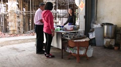 People ordering noodles at street diner of shuanglang in Dali Stock Footage