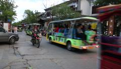 Bikes and vehicles on a busy street in Dali old town Stock Footage