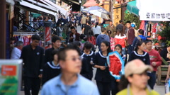 Students in school uniforms walking on a busy street in Dali old town, Yunnan Stock Footage