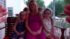 A young pregnant woman, and four children, have their picture taken while sittin Stock Footage