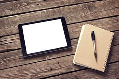 Tablet and notepad on desktop Stock Photos
