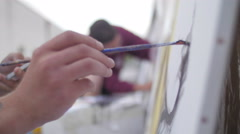 Painter painting with brush on canvas Stock Footage