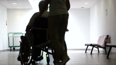 Nurse pushing a man in a wheel chair, backlighting. - stock footage