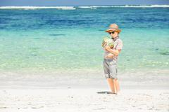 Happy young boy staying on beautiful ocean beach wearing hat and sunglasses - stock photo