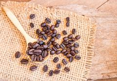 Roasted coffee beans in a wooden spoonl - stock photo