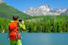 Young man takes a photo of mountain lake, Slovakia Stock Photos