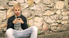 Boy sitting next to the brick wall and texting on smartphone - stock footage