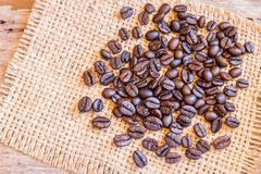 Roasted coffee beans on burlap sack - stock photo