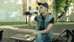 Guy on a park bench drinking Pepsi Cola and eat cookies. Stock Footage