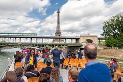 Tourists at river cruise admiring Eiffel tower Paris Stock Photos