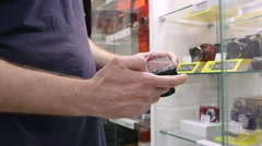 Customer testing new compact camera at photographic equipment store Stock Footage