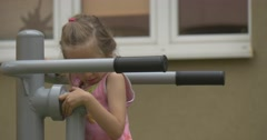Girl Tries to Carry Out Sports Exercises on Bars Stock Footage