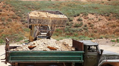 Excavator loading heavy duty dumper truck with rocks Stock Footage