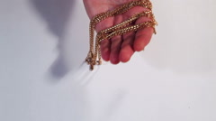Gold chain in a hand on a white background Stock Footage