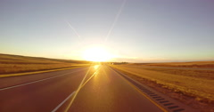 Driving down a highway at sunset along wheat fields - stock footage