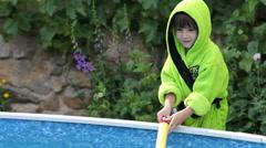 Cute little boy in green beach towel, splashing water with water gun Stock Footage