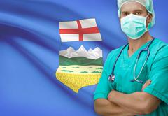 Surgeon with Canadian province flag on background - Alberta - stock photo