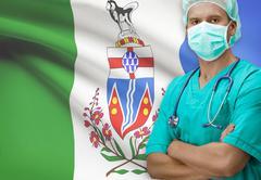 Surgeon with Canadian province flag on background - Yukon - stock photo