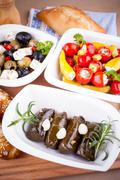 Vine leaves stuffed with peppers and Mediterranean antipasto - stock photo