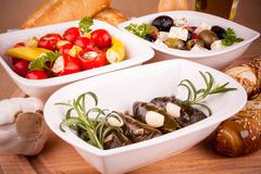Vine leaves stuffed with peppers and Mediterranean antipasto Stock Photos