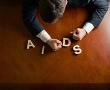 Word AIDS and devastated man composition - stock photo