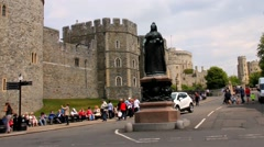 Medieval Windsor Castle with a statue of Queen Victoria on a plinth in the road Stock Footage