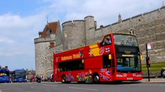 General view of the street with red touristic bus on Medieval Windsor Castle bac Stock Footage