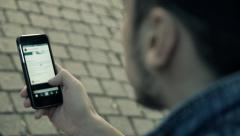 Man sitting in the park and looking at the phone. Instagram Stock Footage