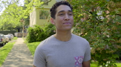 Young Man, Daydreams, Walks Around Neighborhood, Smiling (Slow Motion) Stock Footage