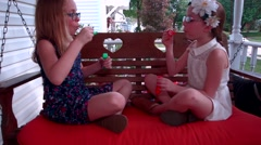 Two little girls play with bubbles as two young boys sneak up behind them while Stock Footage