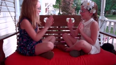 Two little girls play clapping hands and singing while sitting on a porch swing Stock Footage