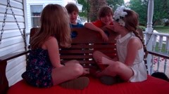 Two little girls and boys sit and talk on a porch swing in the middle of summer Stock Footage