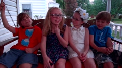 Two little girls and boys sit and talk on a porch swing with their arms around e Stock Footage