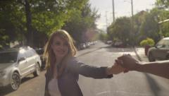 Young Man Dances With His Girlfriend, Spins Her Around, While On A Walk - stock footage