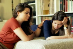 Woman comforting her unhappy friend at home  friends, sitting, home, sofa, house Stock Footage