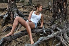 Stock Photo of Teen girl sitting on roots of tree in pine forest