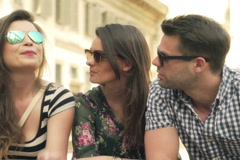 Friends sitting in the city and pointing on something Stock Footage