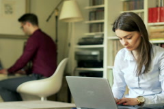 Businesscouple working on laptops at home Stock Footage