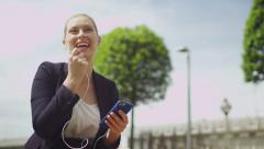 Attractive businesswoman talks on her phone whilst relaxing outside - stock footage