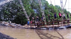 Adventure and Obstacle Race, on Rope swinging over mud pit Stock Footage