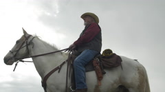 Senior cowboy on Horse - low angle Dolly Left -up Stock Footage